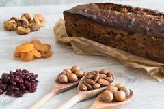 Dolce di Cristmas di frutti sulla tavola di legno grigio chiaro, sui frutti secchi e sui dadi intorno al dolce immagine stock