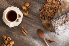 Dolce di Cristmas di frutti sulla tavola di legno di marrone scuro Cannella, anice stellato, fichi e tazza di tè fotografie stock