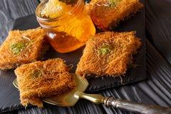 Dolce di Kataif con i pistacchi e la macro fresca del miele su una tavola Uff fotografie stock