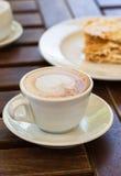 Dolce di millefoglie, caffè del cappuccino su una tavola di legno sulla veranda nel caffè, nel giardino Fotografia Stock