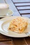 Dolce di millefoglie, caffè del cappuccino su una tavola di legno sulla veranda nel caffè, nel giardino Immagini Stock Libere da Diritti