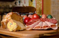 Dolce di Pasqua, salsiccia ed uova rosse su un bordo di legno Fotografie Stock Libere da Diritti
