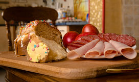 Dolce di Pasqua, uova dipinte e salsiccia sulla tavola nella cucina Immagine Stock