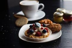 Dolce dolce con la tazza di tè isolata su bianco Fotografia Stock