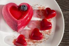 Dolce e caramella sotto forma di un cuore su un piatto bianco Immagine Stock