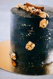 Dolce festivo nero, nello stile dello spazio, con le noci, la cannella e l'anice Immagine Stock