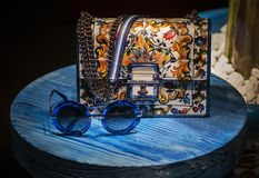 Dolce & Gabbana small woman  bag colorfully colored. Dolce & Gabbana small bag colorfully in retro vintage forms. on the small blue table are blue sun Royalty Free Stock Photography