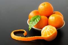 Dolce inacidisca l'arancia e la foglia sbucciate del mandarino sul piatto Immagini Stock Libere da Diritti
