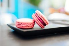 Dolce, macarons freschi con caff? in una tazza blu su una tavola nera fotografie stock libere da diritti