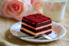 Dolce rosso del velluto con la bella tazza di tè sul fondo marrone del panno fotografia stock