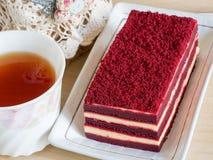 Dolce rosso del velluto sulla tavola e sulla tazza di legno di tè fotografia stock
