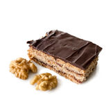 Dolce stratificato con cioccolato sulla cima con le noci isolate su bianco Fotografia Stock