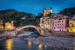 Dolceacqua town at dusk, Liguria, Italy. 15th century Romanesque bridge Ponte Vecchio, over the Nervia creek, colorful houses and ruins of the 13th century Stock Photo