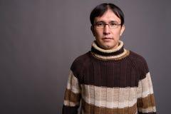 Dolcevita d'uso del giovane uomo asiatico del nerd contro il BAC grigio immagine stock libera da diritti