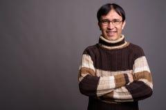 Dolcevita d'uso del giovane uomo asiatico del nerd contro il BAC grigio fotografia stock