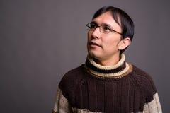 Dolcevita d'uso del giovane uomo asiatico del nerd contro il BAC grigio fotografie stock libere da diritti