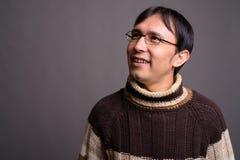 Dolcevita d'uso del giovane uomo asiatico del nerd contro il BAC grigio immagini stock libere da diritti