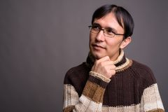 Dolcevita d'uso del giovane uomo asiatico del nerd contro il BAC grigio fotografie stock
