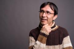 Dolcevita d'uso del giovane uomo asiatico del nerd contro il BAC grigio immagini stock