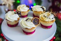 Dolci, bigné con il limone secco e cioccolato su un piedistallo bianco su un fondo del Natale verde ghirlanda e luci Fotografia Stock