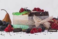 Dolci decorati con i lamponi, pere, biscotti, uva, melograni su un fondo bianco fotografia stock