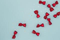Dolci del cioccolato avvolti in carta rossa su fondo blu Fotografia Stock Libera da Diritti