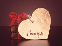 Dolci del cioccolato con il nastro rosso ed il cuore di legno del ` s del biglietto di S. Valentino per il giorno del ` s del big fotografia stock libera da diritti