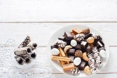 Dolci del cioccolato sulla disposizione bianca del piano del fondo Immagini Stock