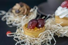 Dolci deliziosi, crema in un vaso della pasticceria dello shortcrust e le due metà principali della ciliegia più delicata immagine stock
