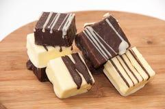 Dolci di cioccolato in bianco e nero su un bordo di legno della cucina Immagine Stock