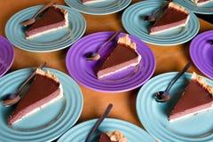 Dolci di cioccolato deliziosi affettati sui piatti variopinti sul fondo di legno della tavola Fotografie Stock