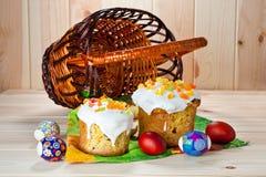 Dolci di Pasqua ed uova dipinte su una tavola di legno Immagini Stock