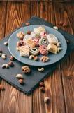 Dolci e dadi orientali tradizionali: nocciole, anacardii su un fondo di legno marrone Il dessert turco è il luogo di Immagini Stock