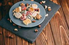 Dolci e dadi orientali tradizionali: nocciole, anacardii su un fondo di legno marrone Il dessert turco è il luogo di Fotografie Stock Libere da Diritti