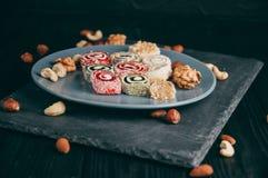 Dolci e dadi orientali tradizionali: nocciole, anacardii su un fondo di legno scuro Il dessert turco è il Rakhat Fotografie Stock Libere da Diritti