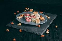 Dolci e dadi orientali tradizionali: nocciole, anacardii su un fondo di legno scuro Il dessert turco è il Rakhat Fotografia Stock