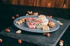 Dolci e dadi orientali tradizionali: nocciole, anacardii su un fondo di legno scuro Il dessert turco è il Rakhat Immagini Stock Libere da Diritti