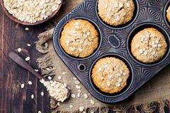 Dolci sani dei muffin, della mela e della banana dell'avena del vegano nella vista superiore della pentola d'annata Immagini Stock