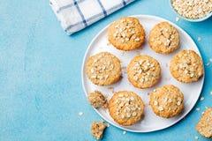 Dolci sani dei muffin, della mela e della banana dell'avena del vegano su una vista superiore del piatto bianco Fotografie Stock