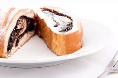 Dolci saporiti del rotolo del cacao spruzzati con zucchero su un piatto con una forcella, isolata su fondo bianco immagini stock libere da diritti
