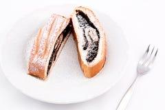 Dolci saporiti del rotolo del cacao spruzzati con zucchero su un piatto con una forcella, isolata su fondo bianco immagine stock
