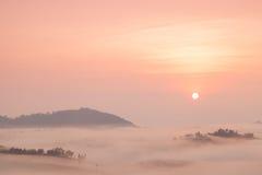 Dolda berg för dimma och resningsolen royaltyfria bilder