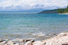 Dolda berg för snö med den blåa sjön Royaltyfri Fotografi