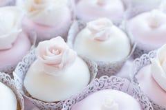 Dolda muffin för fondant med ätliga rosor överst arkivfoto