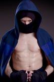 Dolde praktiserande kampsporter för man hans framsida bak en maskering Fotografering för Bildbyråer