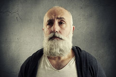 Doleful senior man over dark wall Royalty Free Stock Photography