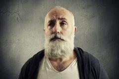 Doleful senior man over dark wall Royalty Free Stock Photography