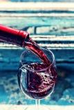 Dolewania czerwone wino w szkło przeciw drewnianemu tłu obrazy stock