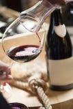 Dolewania czerwone wino w szkło przeciw drewnianemu tłu Fotografia Royalty Free