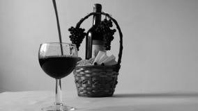 Dolewania czerwone wino w szkło, szorstkiego Butelka czerwone wino, winogrona i pykniczny kosz z serów plasterkami na tle, zbiory